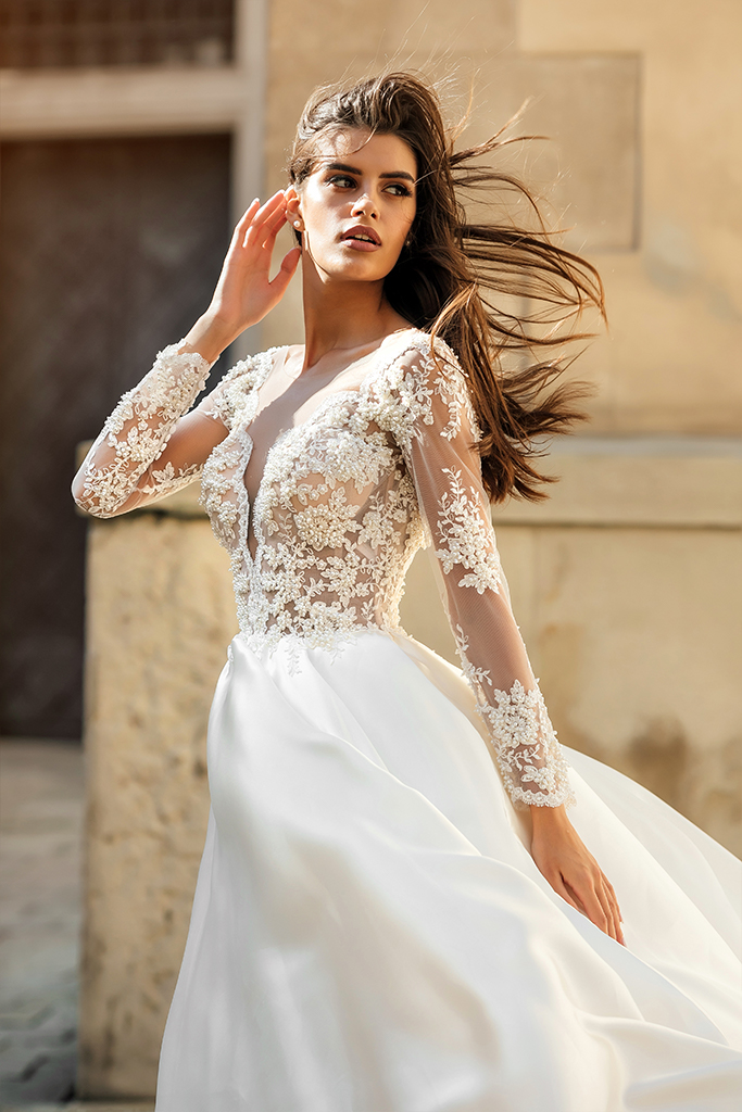 Wedding dresses Aimi Collection  City Passion  Silhouette  A Line  Color  White  Neckline  Portrait (V-neck)  Sleeves  Long Sleeves  Fitted  Train  With train - foto 3